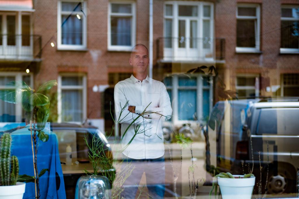 Foto van eigenaar Jeroen Potters achter raam van kantoorpand