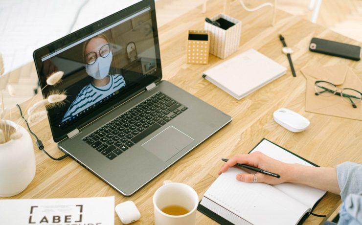 Videobellen in corona tijd vrouw met mondkapje op MacBook